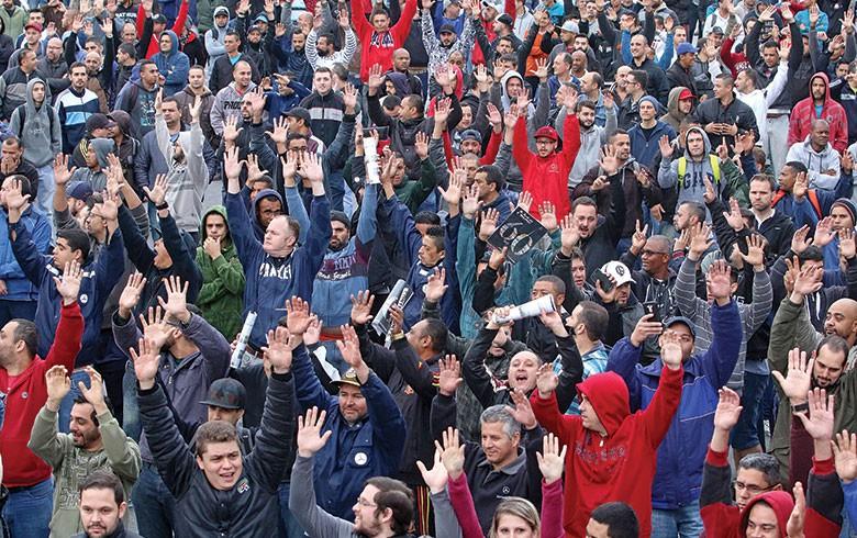 Trabalhadores de mãos erguidas